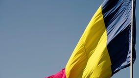 Bandeira romena no vento em um dia ensolarado com o céu azul claro