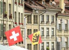 Bandeira suíça e bandeira de Berna na construção da fachada em Berna, Swit Imagens de Stock