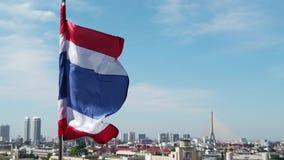 Bandeira tailandesa que move o movimento lento com o vento sobre a cidade de Banguecoque vídeos de arquivo
