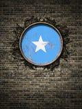 Bandeira velha de Somália na parede de tijolo Fotos de Stock