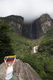 A bandeira venezuelana nas mãos da mulher em Angel Fall, Venezuela Fotos de Stock Royalty Free