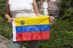A bandeira venezuelana nas mãos da mulher em Angel Fall, Venezuela Imagem de Stock