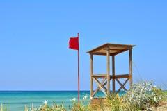 A bandeira vermelha e a casa da salva-vidas Fotos de Stock Royalty Free