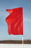 A bandeira vermelha vibra no vento no fundo do céu Imagem de Stock Royalty Free
