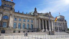 Bandeiras alemãs que acenam no vento na construção de Reichstag, assento do parlamento alemão Deutscher Bundestag, em um dia enso Foto de Stock