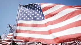 Bandeiras americanas de movimento lento que acenam com um fundo do céu azul Fundo do grunge da independência Day filme