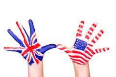 Bandeiras americanas e inglesas nas mãos. Fotos de Stock Royalty Free