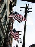 Bandeiras americanas que penduram de uma construção Imagem de Stock Royalty Free