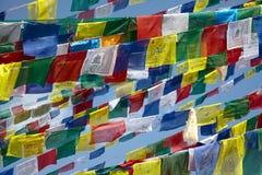 Bandeiras coloridas da oração sobre o fundo do céu azul fotografia de stock