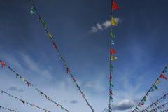 Bandeiras coloridas que bunting contra o céu azul Fotos de Stock Royalty Free