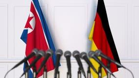 Bandeiras da Coreia do Norte e da Alemanha na reunião ou na conferência internacional rendição 3d Imagens de Stock Royalty Free