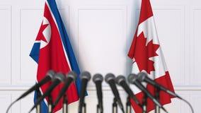 Bandeiras da Coreia do Norte e do Canadá na reunião ou na conferência internacional rendição 3d Fotos de Stock Royalty Free