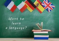 bandeiras da Espanha, do França, da Grâ Bretanha e dos outros países, quadro-negro com texto ' Queira aprender uma língua? ' e li fotos de stock