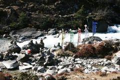 Bandeiras da oração e pedras da oração ao longo do rio Fotografia de Stock