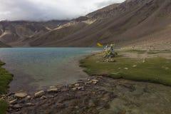 Bandeiras da oração nos bancos do lago chandrataal no vale de Spiti imagens de stock royalty free