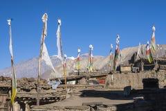 Bandeiras da oração sobre as casas na vila Jharkot Imagem de Stock
