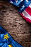 Bandeiras da União Europeia americana e na placa rústica do carvalho Bandeiras da UE e dos EUA junto diagonalmente Imagens de Stock Royalty Free