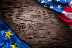 Bandeiras da União Europeia americana e na placa rústica do carvalho Bandeiras da UE e dos EUA junto diagonalmente Fotografia de Stock