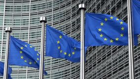 Bandeiras da União Europeia em seguido que acenam no vento, Comissão Europeia filme