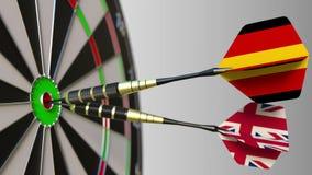 Bandeiras de Alemanha e do Reino Unido nos dardos que batem o bullseye do alvo Cooperação internacional ou fotografia de stock royalty free