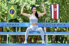 Bandeiras de Brasil e de Costa Rica que estão sendo guardados pela menina 'sexy' bonita imagem de stock royalty free