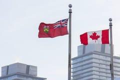 Bandeiras de Canadá e de Ontário na frente dos arranha-céus em Toronto Imagens de Stock