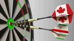 Bandeiras de Canadá e de Irã nos dardos que batem o bullseye do alvo Cooperação internacional ou competição 3D conceptual Imagem de Stock