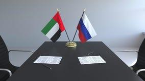 Bandeiras de Emiratos Árabes Unidos e da Rússia e papéis na tabela Negociações e assinatura de um internacional ilustração stock