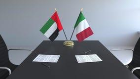 Bandeiras de Emiratos Árabes Unidos e de Itália e papéis na tabela Negociações e assinatura de um acordo internacional ilustração stock