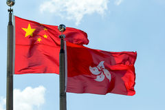 Bandeiras de Hong Kong e de China de lado a lado fotografia de stock