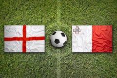 Bandeiras de Inglaterra e de Malta no campo de futebol Imagens de Stock
