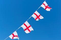Bandeiras de Inglaterra/estamenha contra o céu azul fotografia de stock royalty free