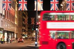 Bandeiras de Londres e ônibus de Londres na noite fotografia de stock royalty free