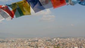 Bandeiras de ondulação da oração contra a arquitetura da cidade Ideia de acenar bandeiras coloridos da oração em cordas acima da  filme