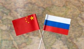 Bandeiras de Rússia e de China sobre o mapa do mundo, imagem do conceito dos países do líder político imagens de stock