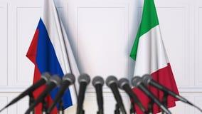 Bandeiras de Rússia e de Itália na conferência internacional da reunião ou de imprensa das negociações video estoque