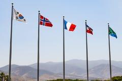 Bandeiras de vários países com as montanhas no fundo fotografia de stock
