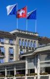 Bandeiras de Zurique e de Suíça no buildin do hotel da laca do au de Baur fotos de stock