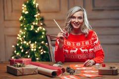 Bandeiras do Natal da pintura da mulher com escova Foto de Stock