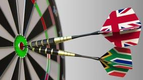 Bandeiras do Reino Unido e da África do Sul nos dardos que batem o bullseye do alvo Cooperação internacional ou fotografia de stock