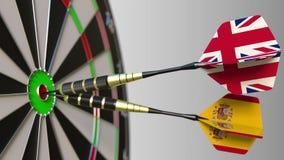 Bandeiras do Reino Unido e da Espanha nos dardos que batem o bullseye do alvo Cooperação internacional ou competição Imagem de Stock