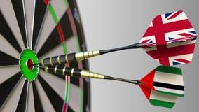 Bandeiras do Reino Unido e dos UAE nos dardos que batem o bullseye do alvo Cooperação internacional ou Fotos de Stock