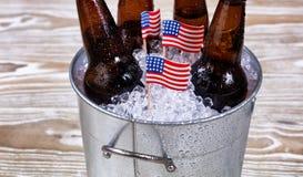 Bandeiras dos EUA do feriado e cubeta da cerveja gelado na madeira rústica Imagem de Stock