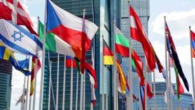 Bandeiras dos países diferentes do mundo contra o centro de negócios vídeos de arquivo