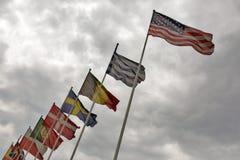 Bandeiras dos países diferentes que acenam contra um céu nebuloso Fotografia de Stock Royalty Free