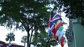 Bandeiras dos países diferentes que penduram na rua sob árvores video estoque
