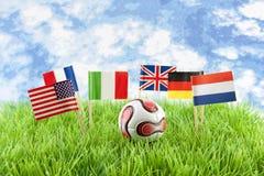 Bandeiras e esfera no campo de futebol fotografia de stock