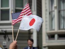 Bandeiras handheld de Japão e de Estados Unidos que estão sendo acenadas imagens de stock