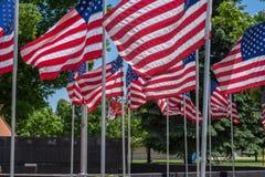 Bandeiras múltiplas dos E.U. nos polos que acenam no vento Foto de Stock