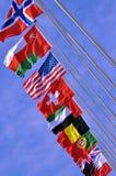 Bandeiras nacionais diferentes sob o céu Imagem de Stock